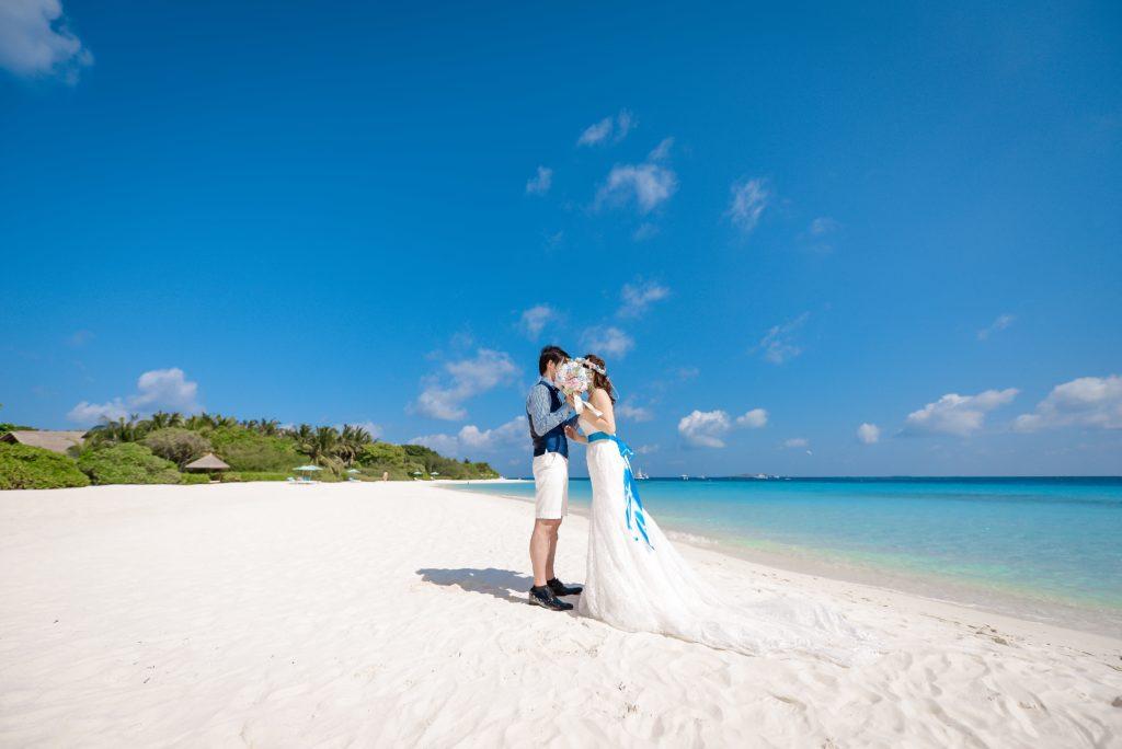 砂浜に立つ新郎新婦のフリー写真素材