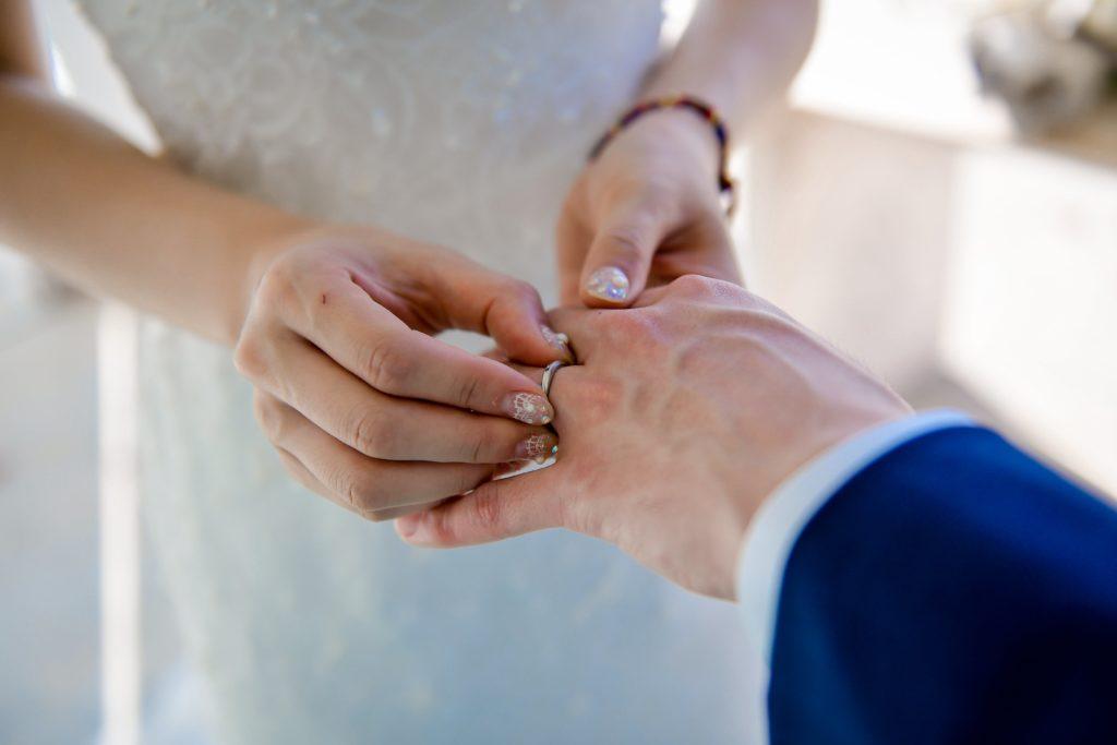 新婦が新郎に指輪をはめるイメージのフリー写真素材