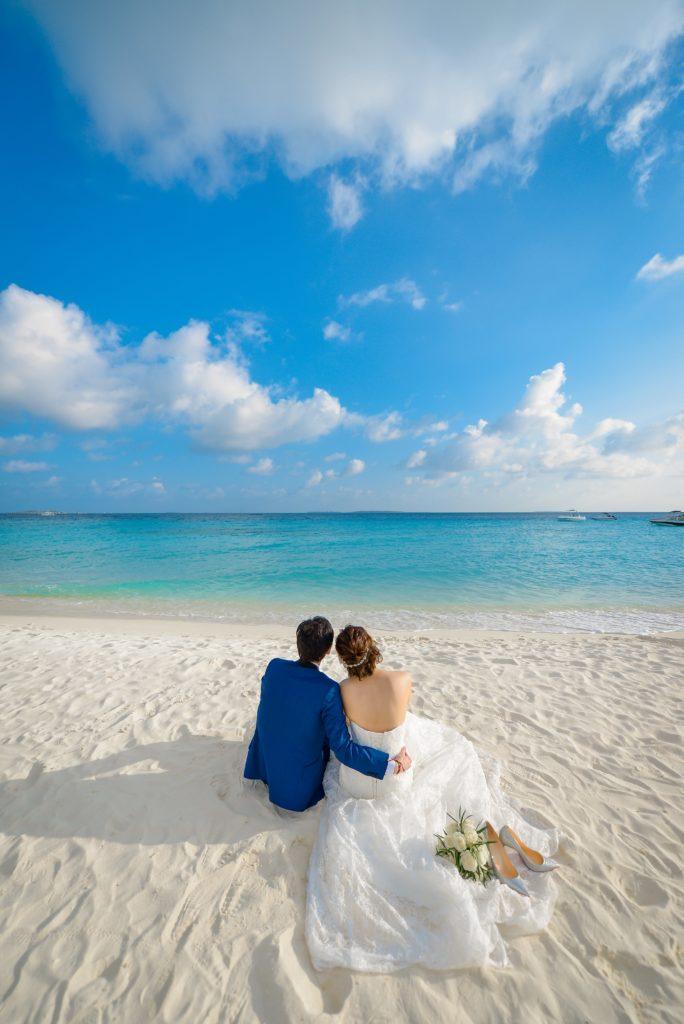 海辺に座る新郎新婦のフリー写真素材