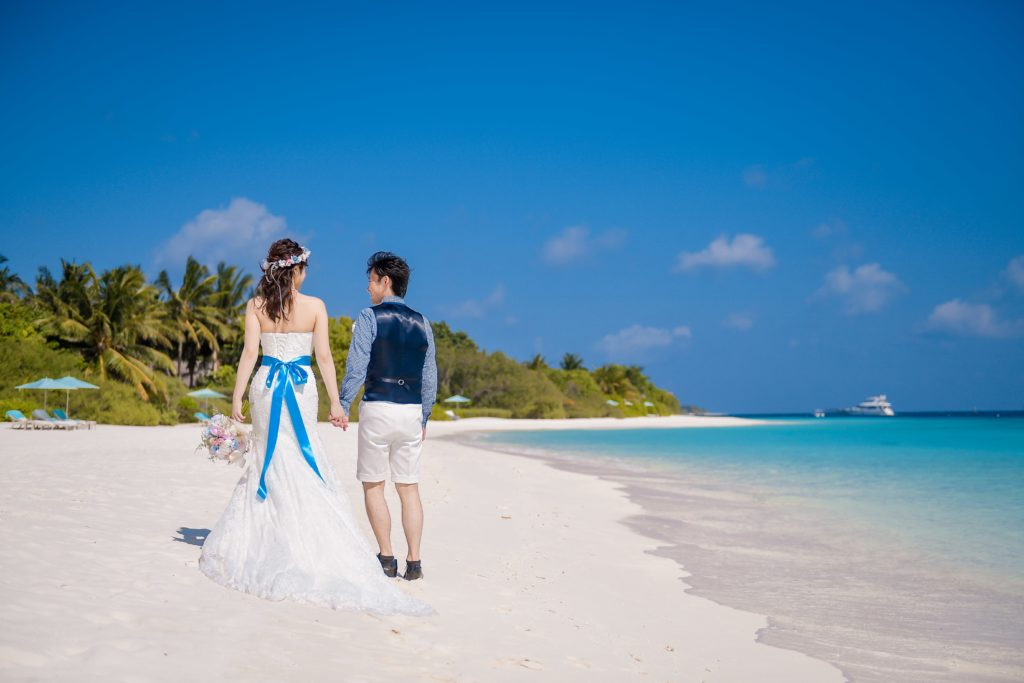 砂浜を歩く新郎新婦のフリー写真素材