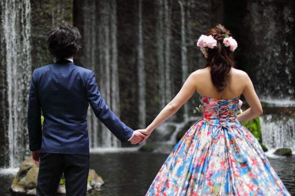 滝の前で手をつなぐ新郎新婦のフリー写真素材