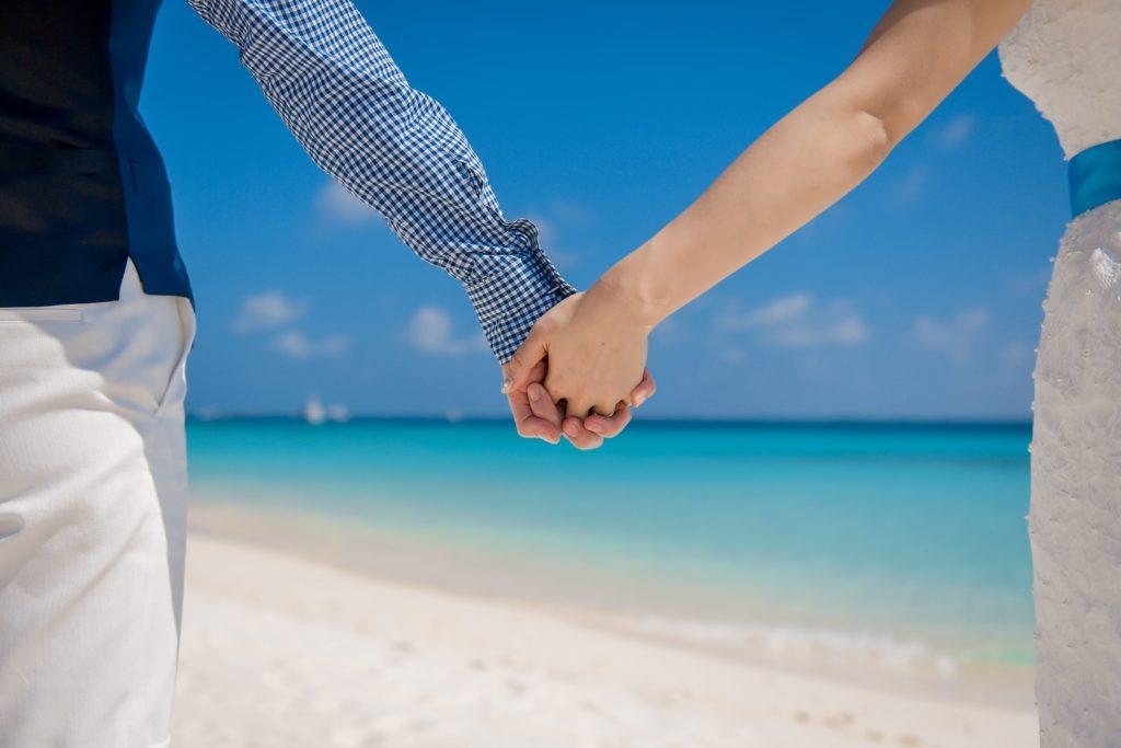 海辺で手をつなぐ新郎新婦のフリー写真素材